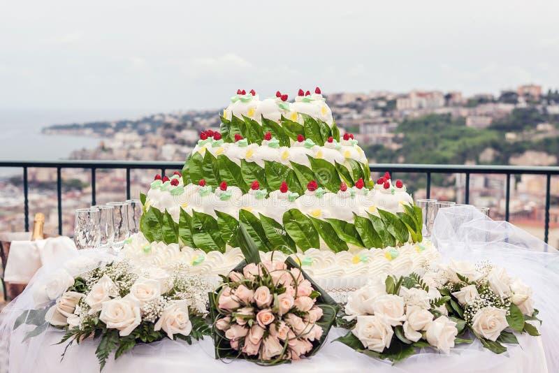 Белое свадебное торт, украшенное красными фруктами и зеленым лимонным листом, флореальная тема стоковые фото