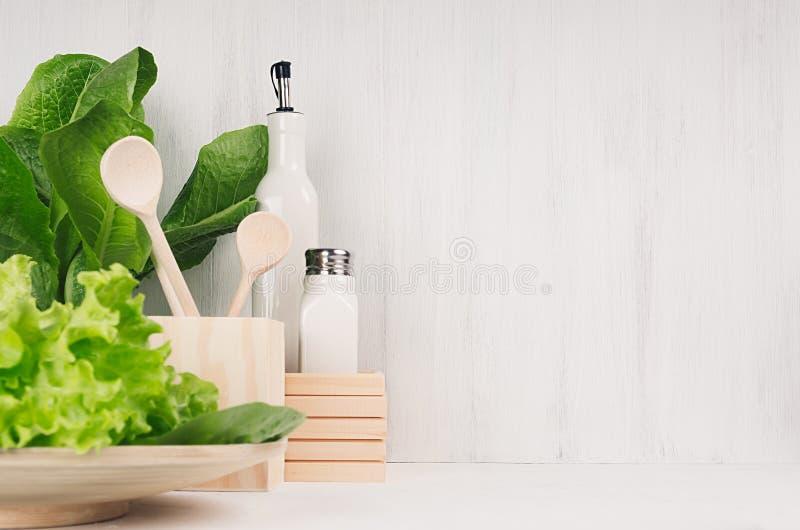 Белое современное оформление кухни с бежевым естественным деревянным блюдом, утварями, свежим зеленым салатом на деревянной предп стоковое фото rf