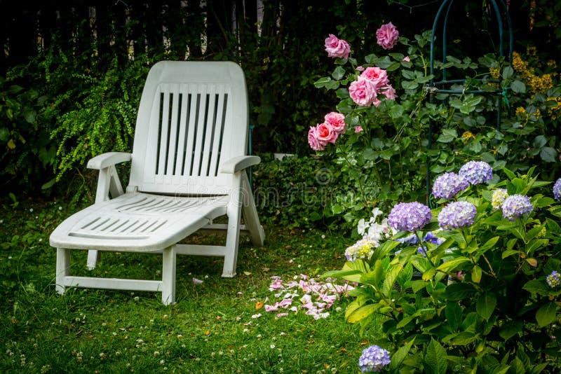 Белое deckchair и красивые цветки в домашнем саде стоковая фотография