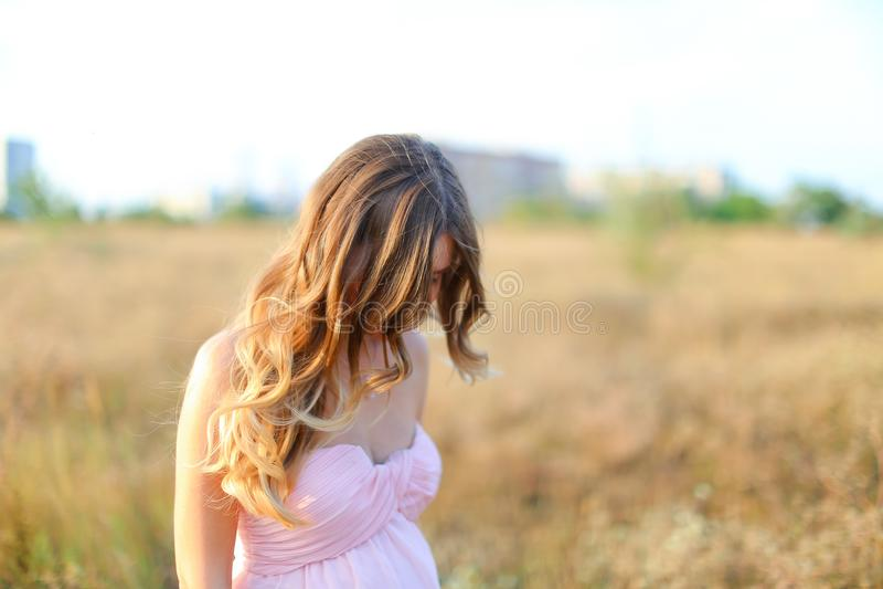 Белокурая беременная женщина нося розовое платье стоя в предпосылке степи стоковое изображение