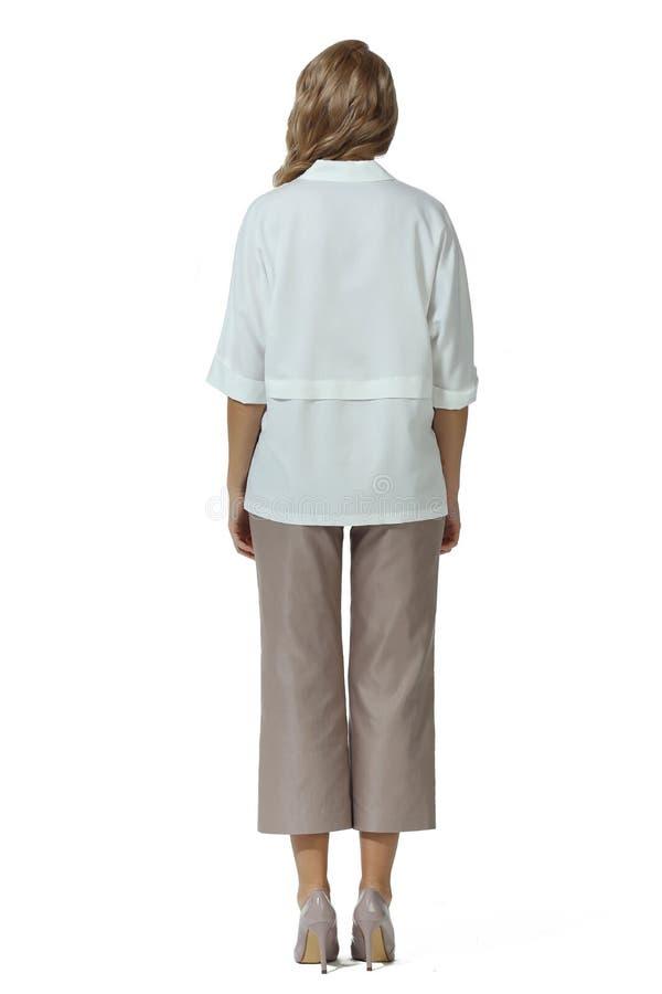 Белокурая бизнес-леди с длинными волосами в ботинках шпилек высоких пяток брюк официальных белых коротких kulottes блузки рукава  стоковые фото