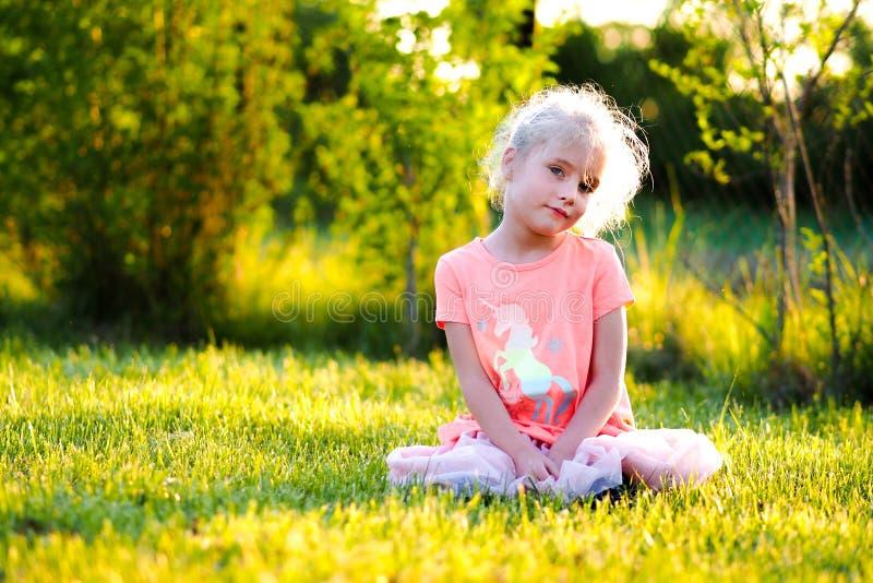 Белокурая голубая наблюданная маленькая девочка играя в парке стоковые фотографии rf