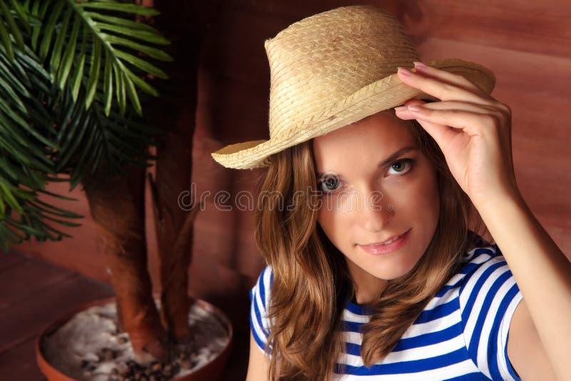 Белокурая дама держа соломенную шляпу и сидя около деревянного дома в s стоковое фото rf