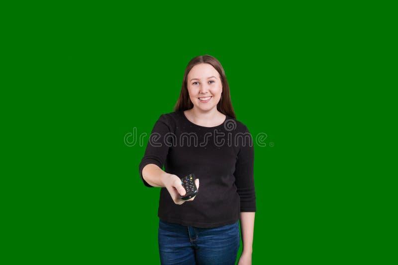 Белокурая дама указывая дистанционное управление телевидения на камеру стоковое изображение