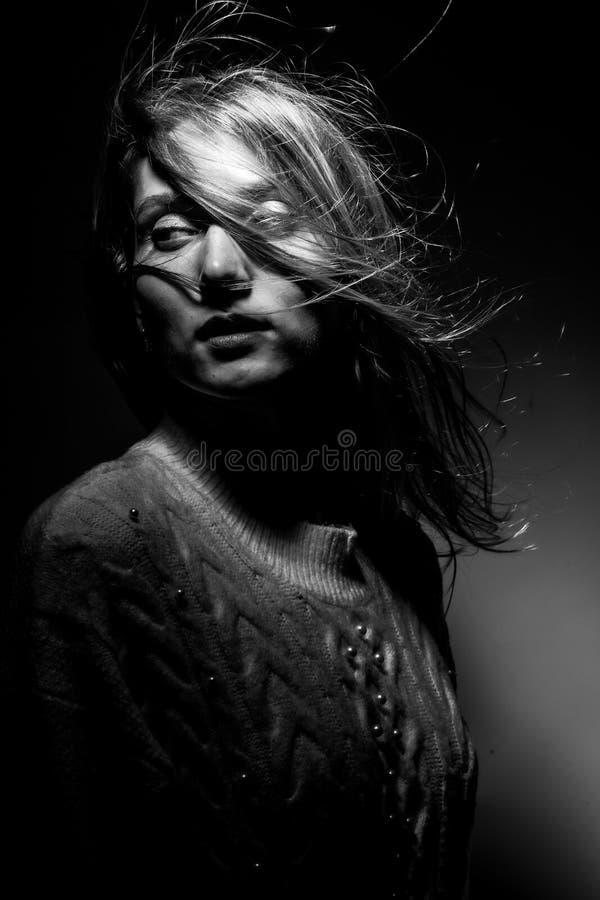 Белокурая девушка в белом свитере на черной предпосылке стоковое фото rf