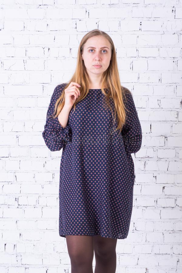 Белокурая девушка в голубом платье с серьезным выражением на ее стороне стоит против белой кирпичной стены стоковое фото rf