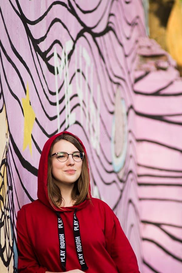 Белокурая девушка в красный усмехаться фуфайки и стекел стоковые фото