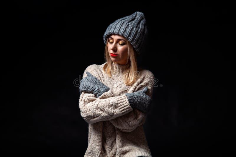 Белокурая девушка в серых перчатках и шляпе и связанном свитере стоит с оружиями сложенными и обнятыми с ее закрытыми глазами стоковое изображение rf