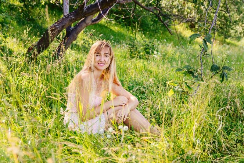 Белокурая девушка на зеленой лужайке лета стоковые фотографии rf
