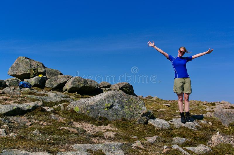 Белокурая девушка при солнечные очки нося атлетические одежды на скалистом саммите на солнечный день стоковая фотография rf