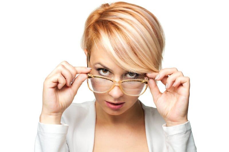 Белокурая девушка смотря над стеклами стоковое фото