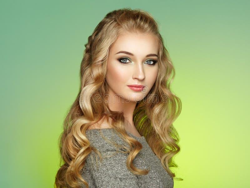 Белокурая девушка с длинным и сияющим вьющиеся волосы стоковая фотография rf