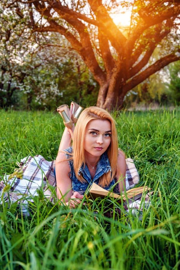 Белокурая девушка с книгой на траве стоковое фото rf