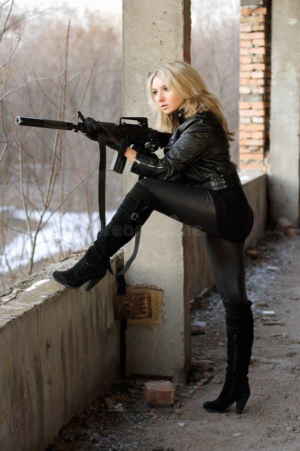 Белокурая девушка с пушкой submachine стоковая фотография rf