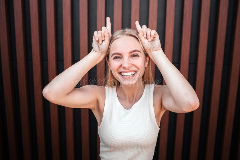 Белокурая девушка stnading и смотрящ на камере Она смеется над Девушка показывает рожки с ее пальцами Изолированный дальше стоковое фото