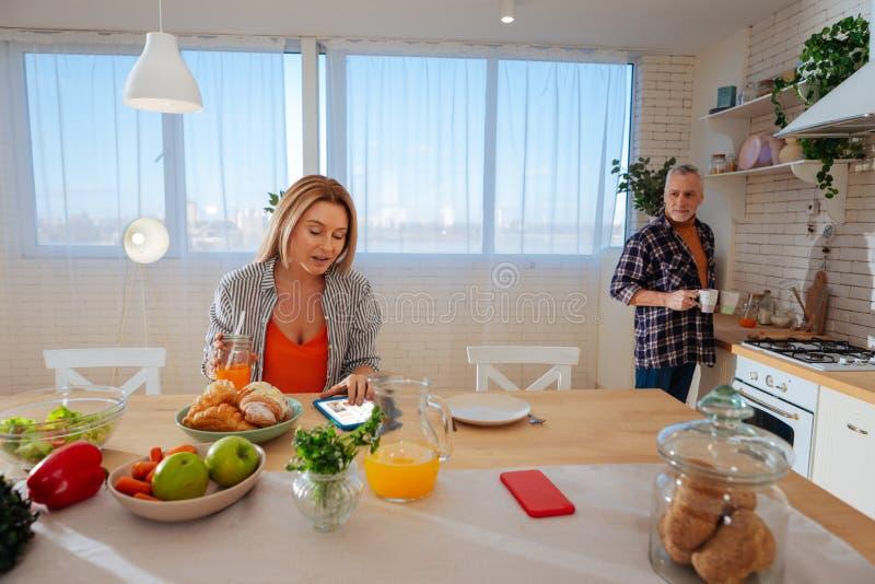 Белокурая жена сидя на таблице в кухне говоря с ее супругом стоковые фотографии rf