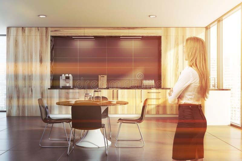 Белокурая женщина в деревянной кухне стоковое фото rf