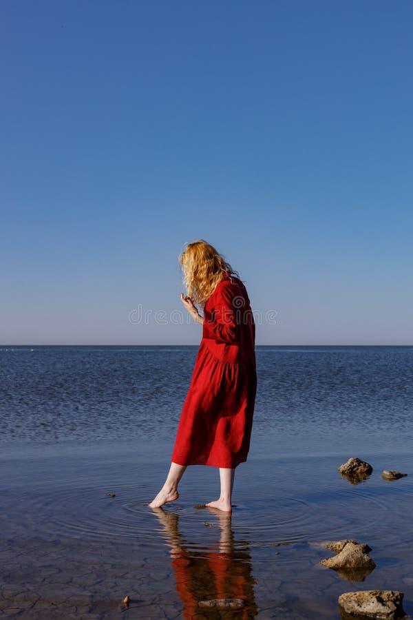 Белокурая женщина в красном длинном положении платья белья в море в утре стоковые изображения rf