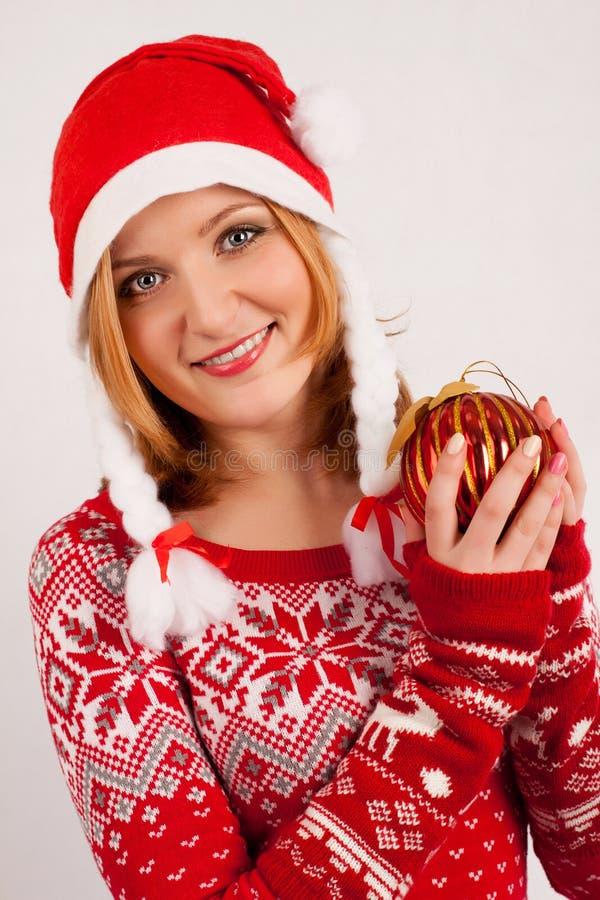 Белокурая женщина в крышке красных свитере ` s Нового Года и ` s Нового Года на белой предпосылке держит шарик рождественской елк стоковые изображения rf