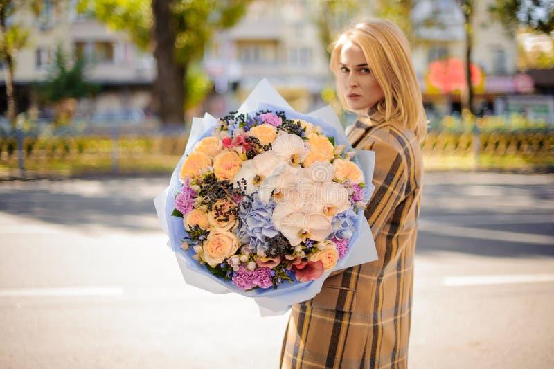 Белокурая женщина в пальто шотландки держа симпатичный большой букет цветков против города стоковое фото rf