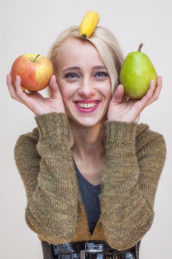 Белокурая женщина держа плодоовощи груши и банана яблока стоковая фотография rf