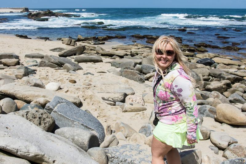 Белокурая женщина исследует изрезанный, скалистый пляж La Jolla Калифорния стоковое изображение rf