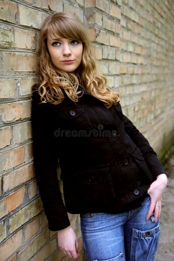 белокурая женщина кирпичной стены стоковая фотография rf
