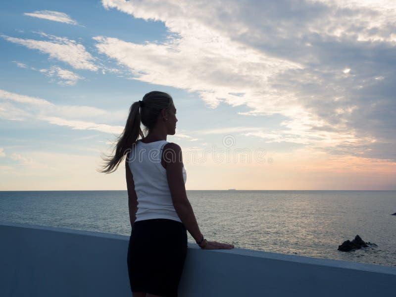 Белокурая женщина наблюдая заход солнца от террасы с видом море стоковые изображения