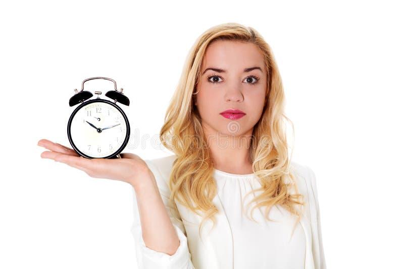 Белокурая женщина показывая будильник, изолированный на белизне стоковое изображение
