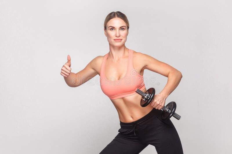 Белокурая женщина показывая как знак и держа гантель стоковые фото