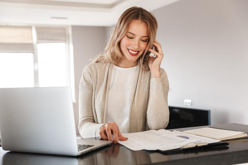 Белокурая женщина представляя сидеть внутри помещения дома используя ноутбук говоря мобильным телефоном стоковые фото