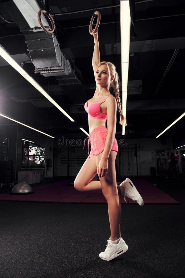 Белокурая женщина представляя с гимнастическими кольцами стоковые фотографии rf