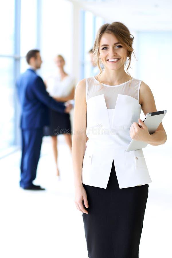 Белокурая женщина при компьютер сенсорной панели смотря камеру и усмехаясь пока бизнесмены тряся руки над предпосылкой стоковое фото rf