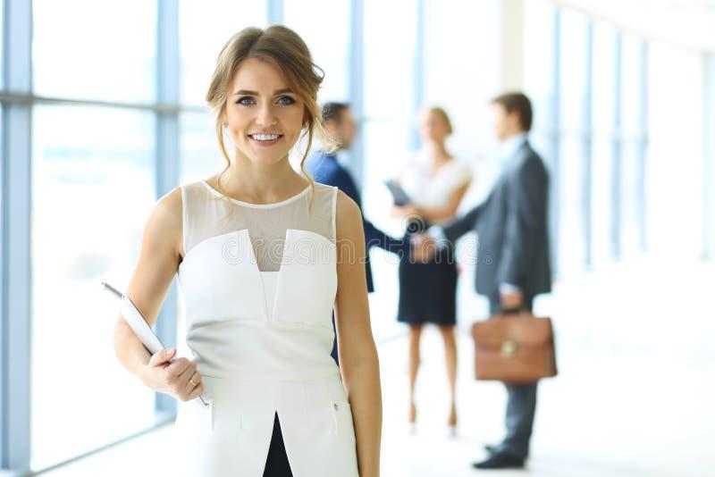 Белокурая женщина при компьютер сенсорной панели смотря камеру и усмехаясь пока бизнесмены тряся руки над предпосылкой стоковая фотография