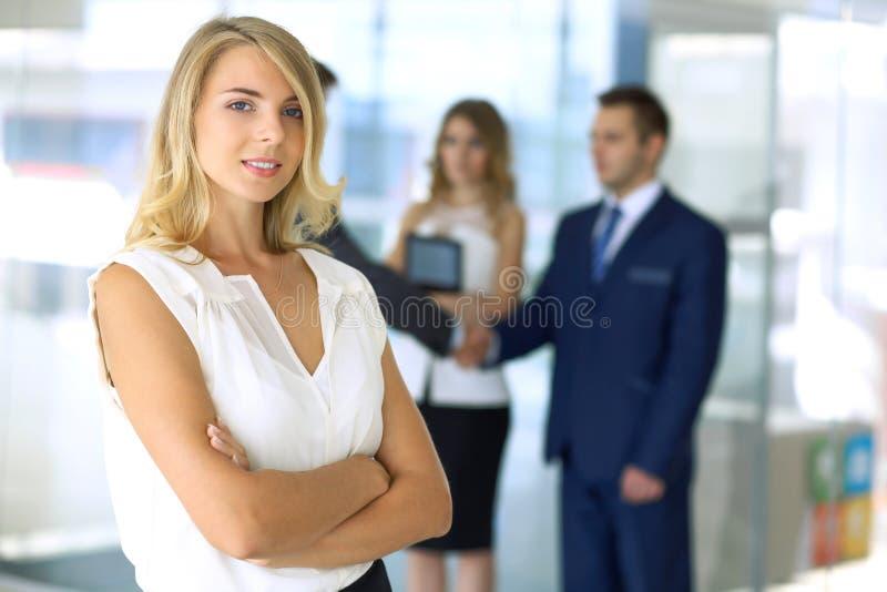 Белокурая женщина при компьютер сенсорной панели смотря камеру и усмехаясь пока бизнесмены тряся руки над предпосылкой стоковое изображение