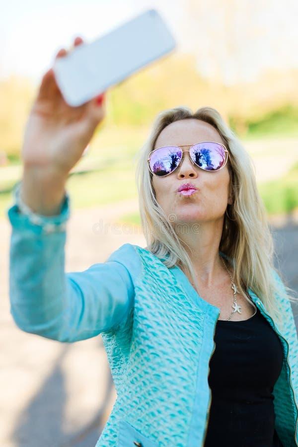 Белокурая женщина со стеклами солнца делая selfie стоковое изображение rf