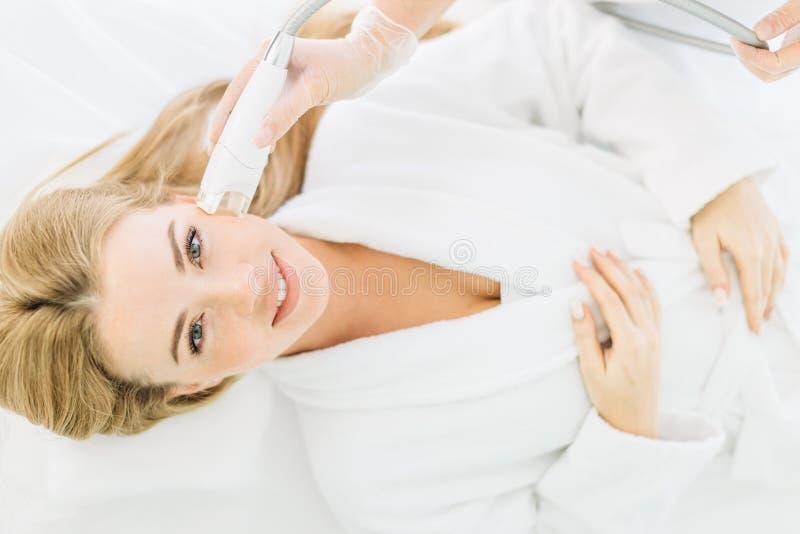 Белокурая женщина с длинными волосами делает лазер стороны resurfacing в центре красоты стоковое фото