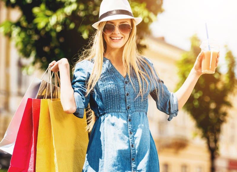 Белокурая женщина с стеклом сока после ходить по магазинам стоковое фото rf