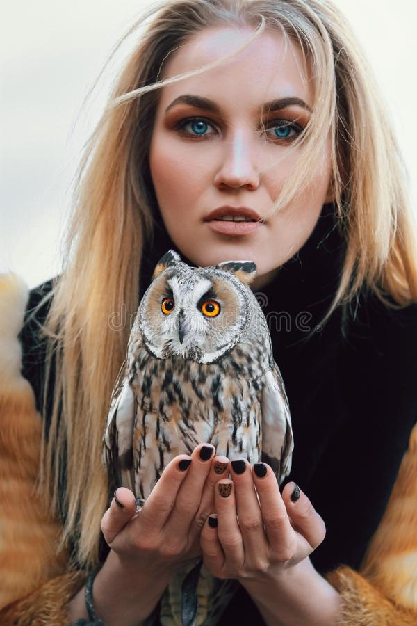 Белокурая женщина с сычом в ее руках идет в древесины в осени и весне Длинная девушка волос, романтичный портрет с сычом стоковое изображение rf