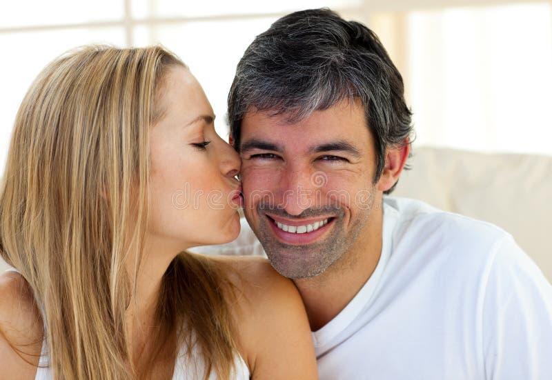 Белокурая женщина целуя ее супруга стоковое фото rf
