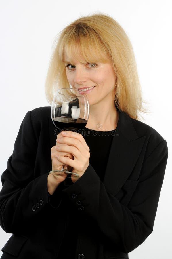 Белокурая исполнительная женщина toasts с стеклом вина с провокационным выражением стоковое фото rf