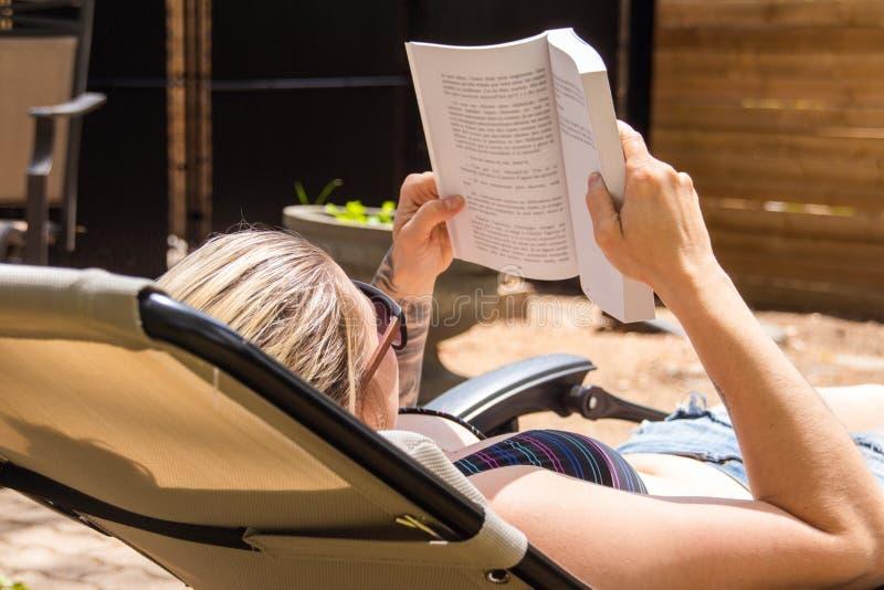 Белокурая книга чтения женщины путем принимать sunbath в задворк дома стоковое изображение