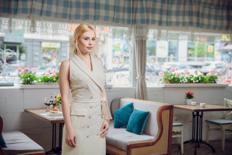 Белокурая красивая коммерсантка представляя в ресторане стоковое фото