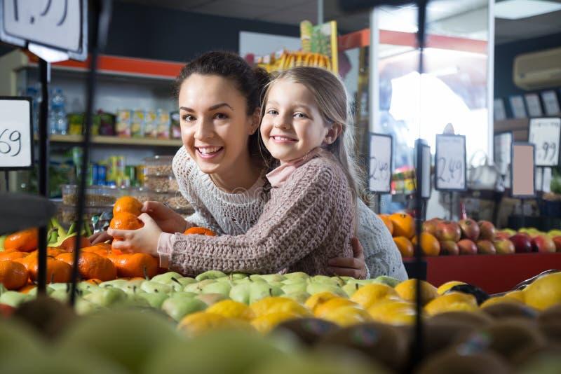 Белокурая маленькая девочка с матерью представляя мандарин whith в плодах отдела магазина стоковые фотографии rf