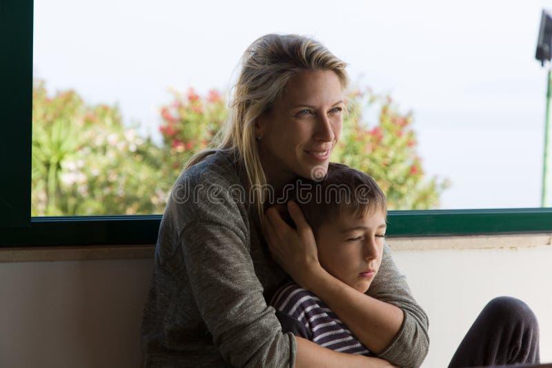 Белокурая мать усмехается и держится ее маленький ребенка между ее оружиями стоковые изображения rf