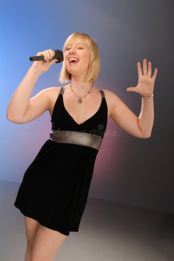 белокурая милая девушка пея стоковая фотография