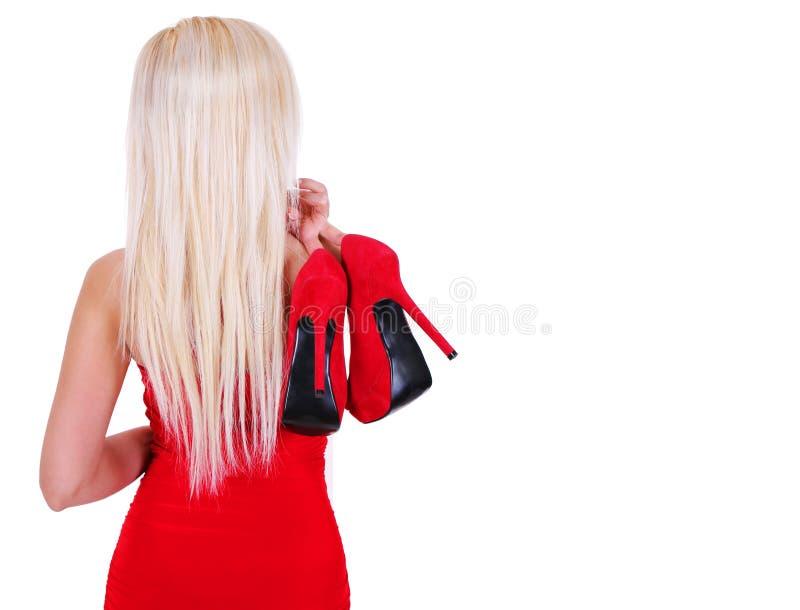 Белокурая молодая женщина держа сексуальные красные ботинки высокой пятки изолировано стоковая фотография rf