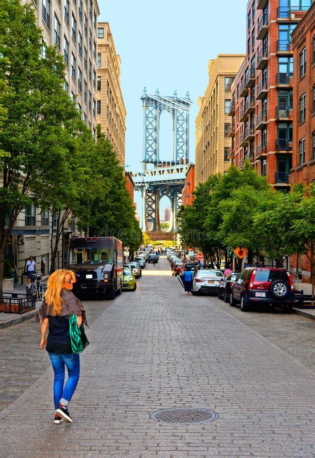 Белокурая молодая женщина идя с предпосылкой зданий моста и кирпичной стены Манхэттена старых и архитектурами в Бруклине в ТУПОМ стоковое фото rf