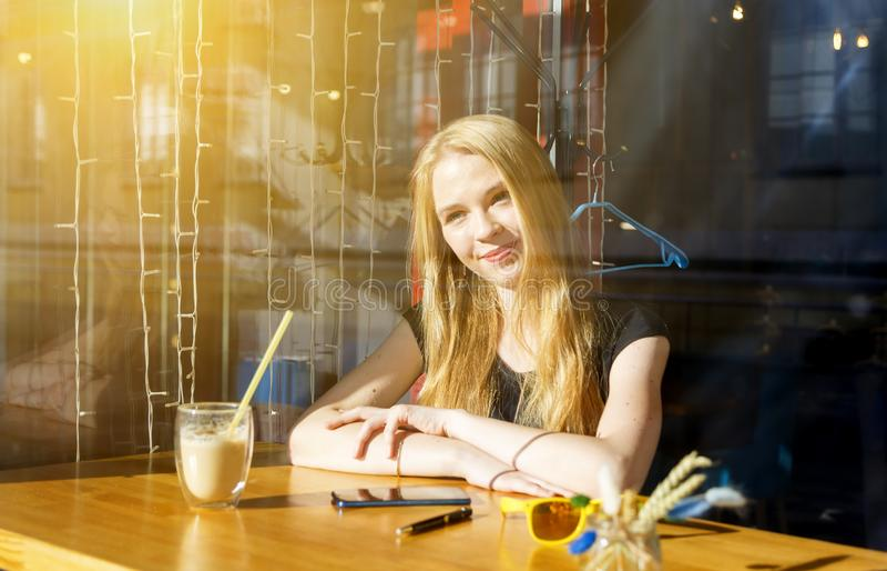 Белокурая молодая женщина с коктейлем или latte на таблице в кафе стоковое фото rf
