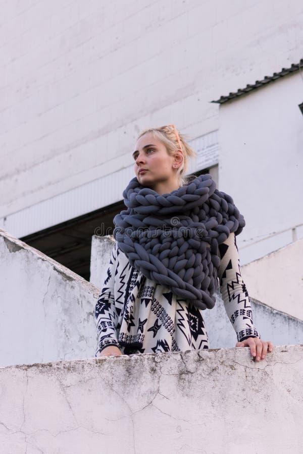 Белокурая молодая красивая девушка моды нося ацтекскую черно-белую куртку и связанный серый шарф жилета Обмундирование фестиваля стоковое изображение rf